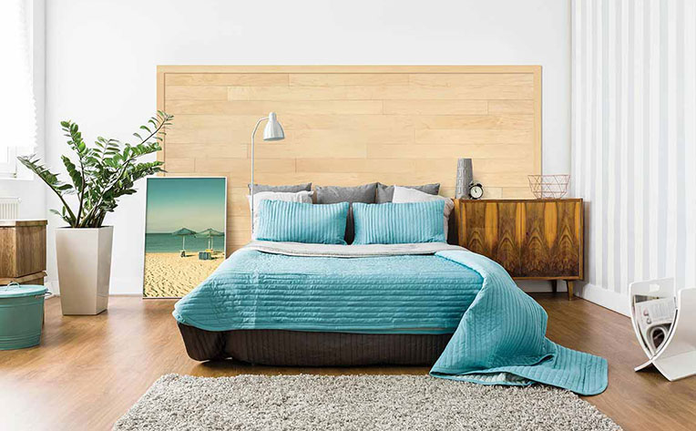Bedroom with teal bedspread and beach photo for a resort look